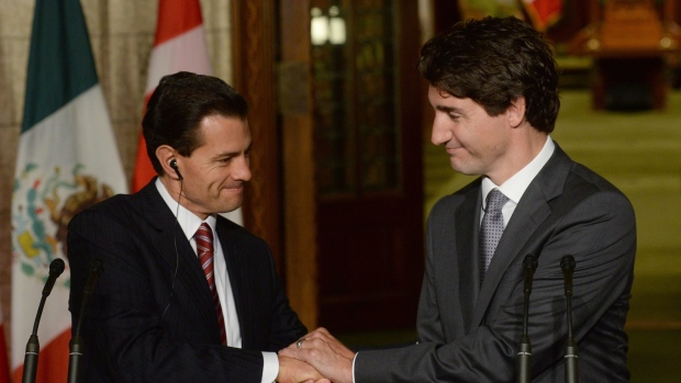 Prime Minister Justin Trudeau and Mexican President Enrique Pena Nieto clasp hands at a joint news conference on Parliament Hill in Ottawa on Tuesday, June 28, 2016. Canada recently dropped a visa requirement for travellers from Mexico.